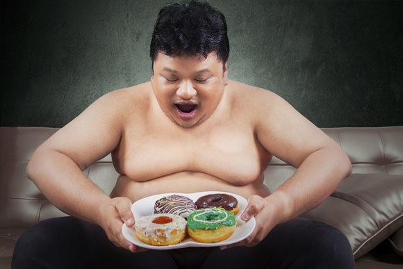 obese man looking at donuts عوامل موثر و دلیل علمی چاقی سلامت