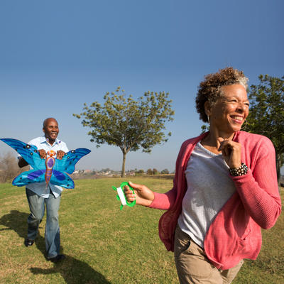 Senior couple running in park with kite