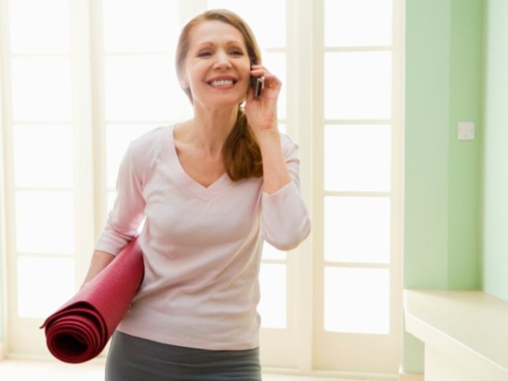تغییر سبک زندگی برای لاغری,woman-holding-yoga-mat-and-cell-phone600x450