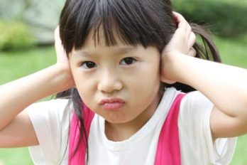 little girl covering her ears and expressing Negativity