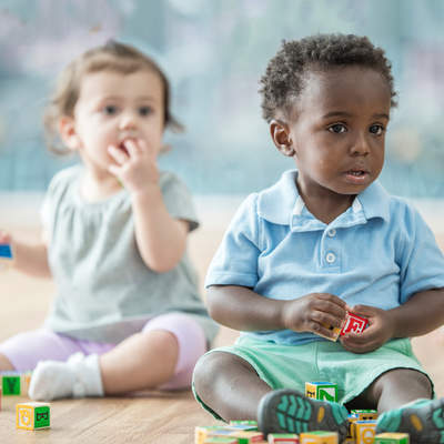 Babies play in a daycare together. They play with blocks. Here, a three babies play together.