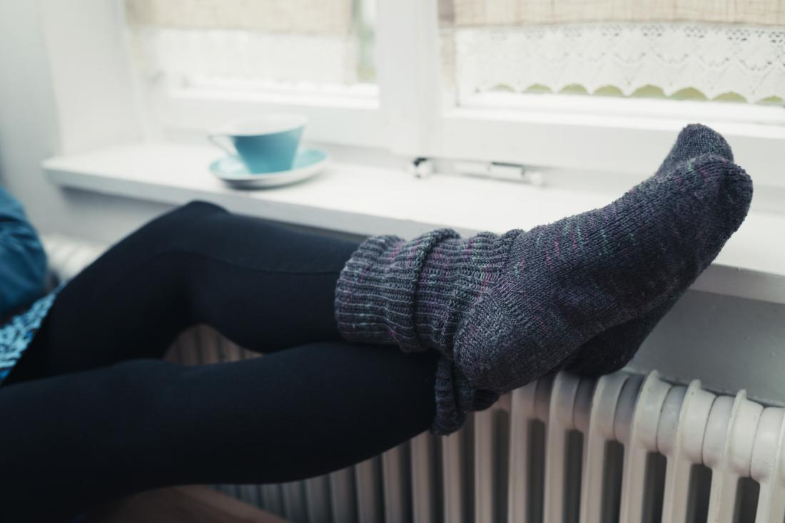person with thick winter socks on cold feet perched on top of radiator heater علت و درمان سردی پاها سلامت